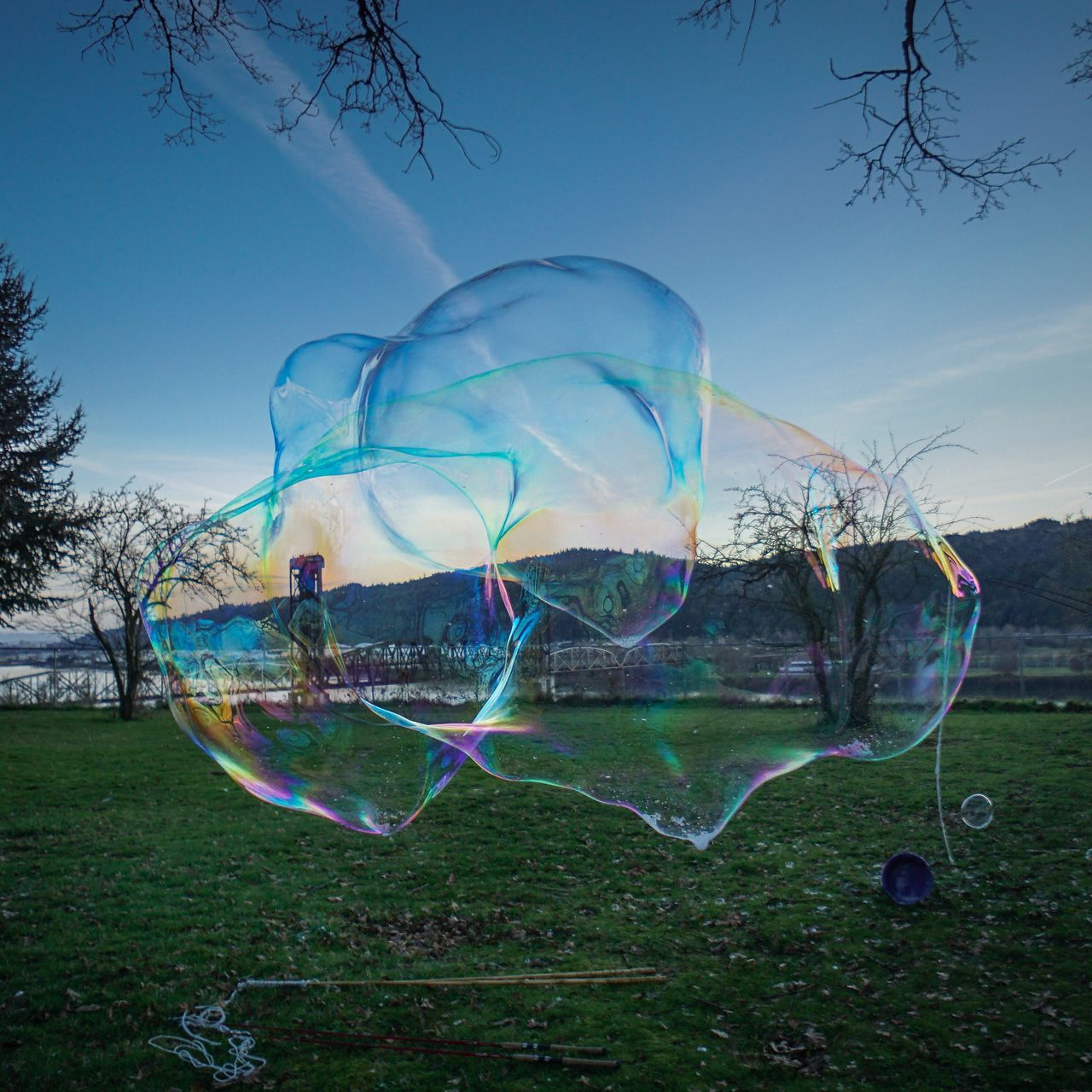 Soap bubbles over field against sky