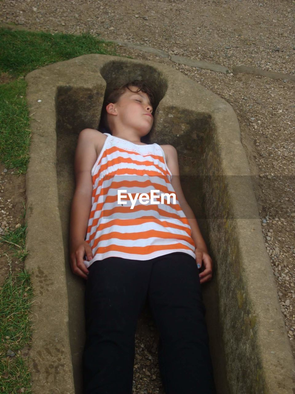 High Angle View Of Boy Sleeping In Grave At Whitby Abbey