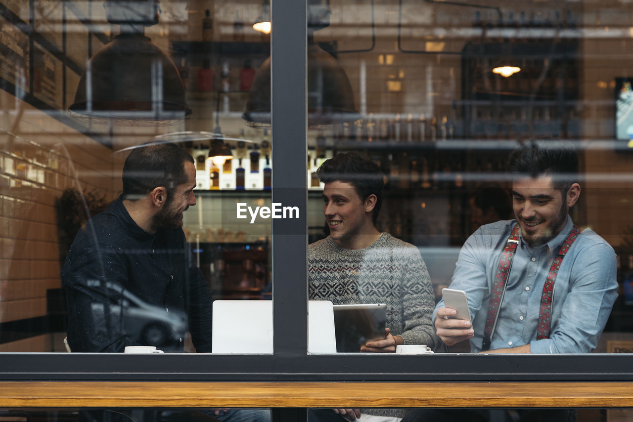 Friends working on laptop while sitting in cafe seen through window