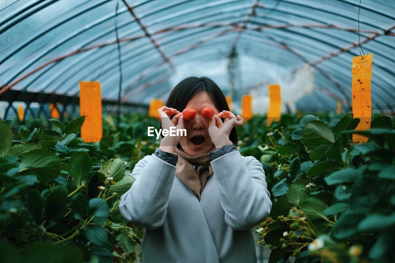Woman Covering Eyes With Strawberries In Greenhouse