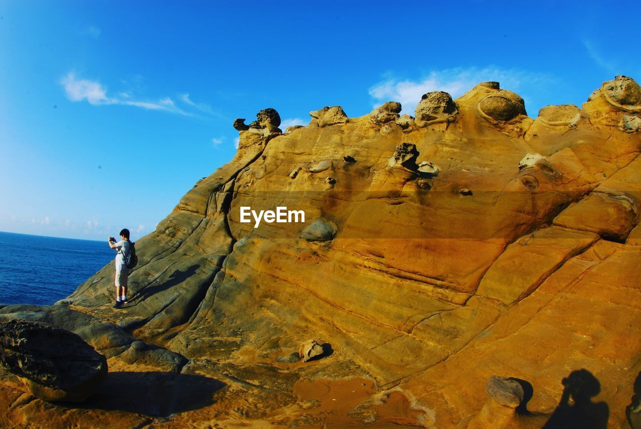 rock, solid, sky, rock - object, beauty in nature, nature, day, rock formation, real people, tranquility, scenics - nature, land, tranquil scene, outdoors, lifestyles, sunlight, water, blue, group of people