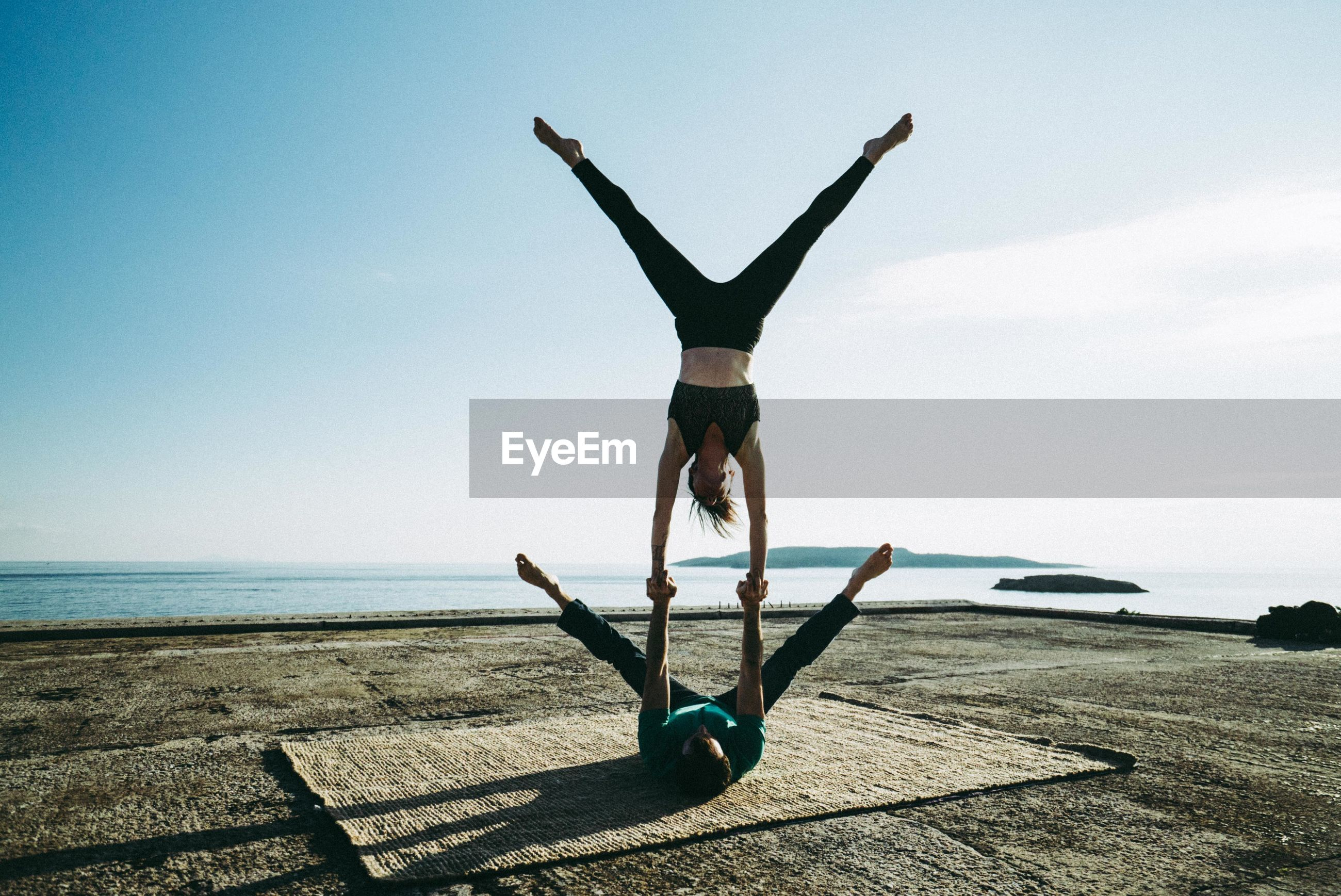 Full length of man balancing woman on hand by sea against clear sky