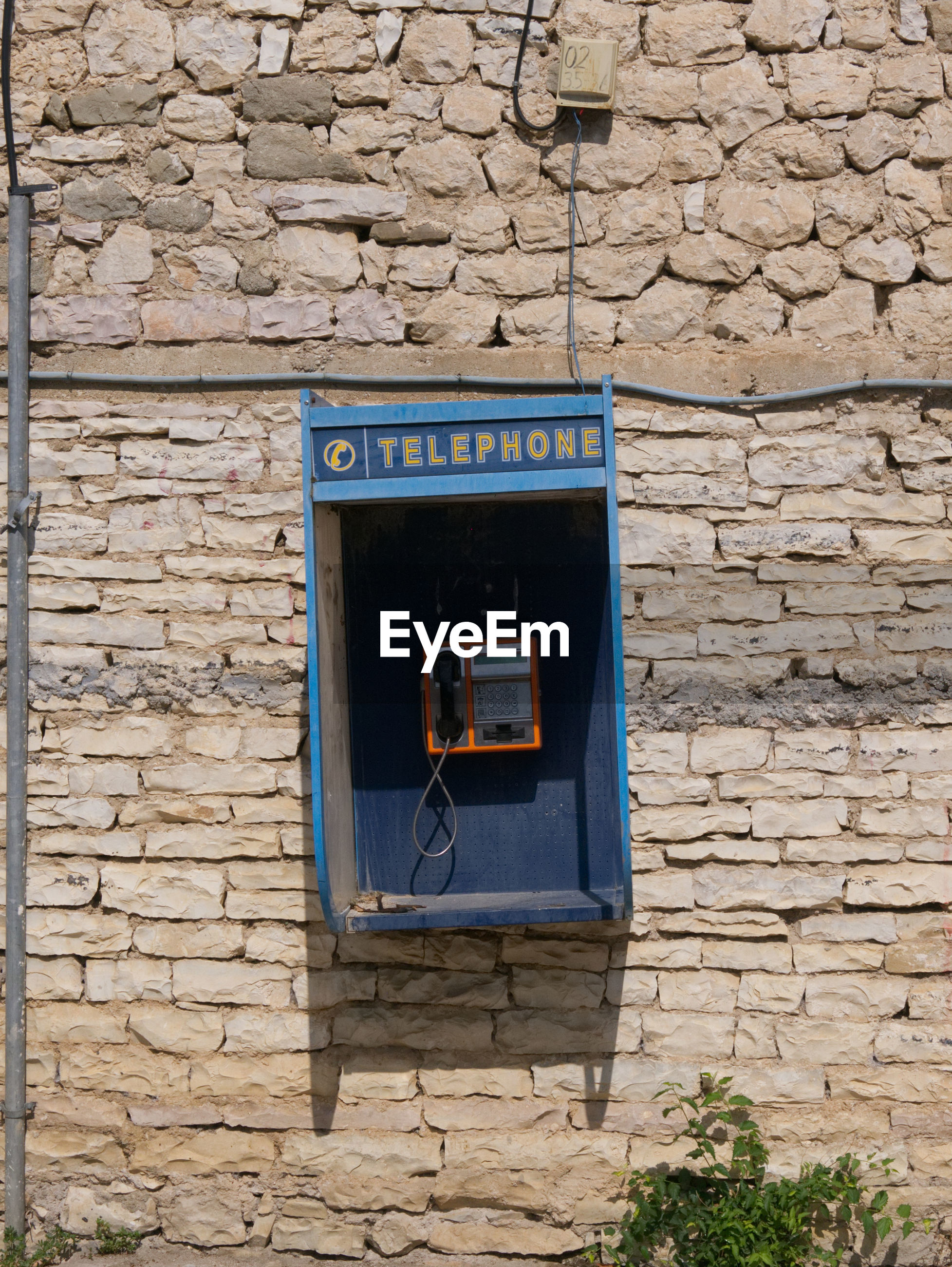 Telephone booth mounted on wall during sunny day