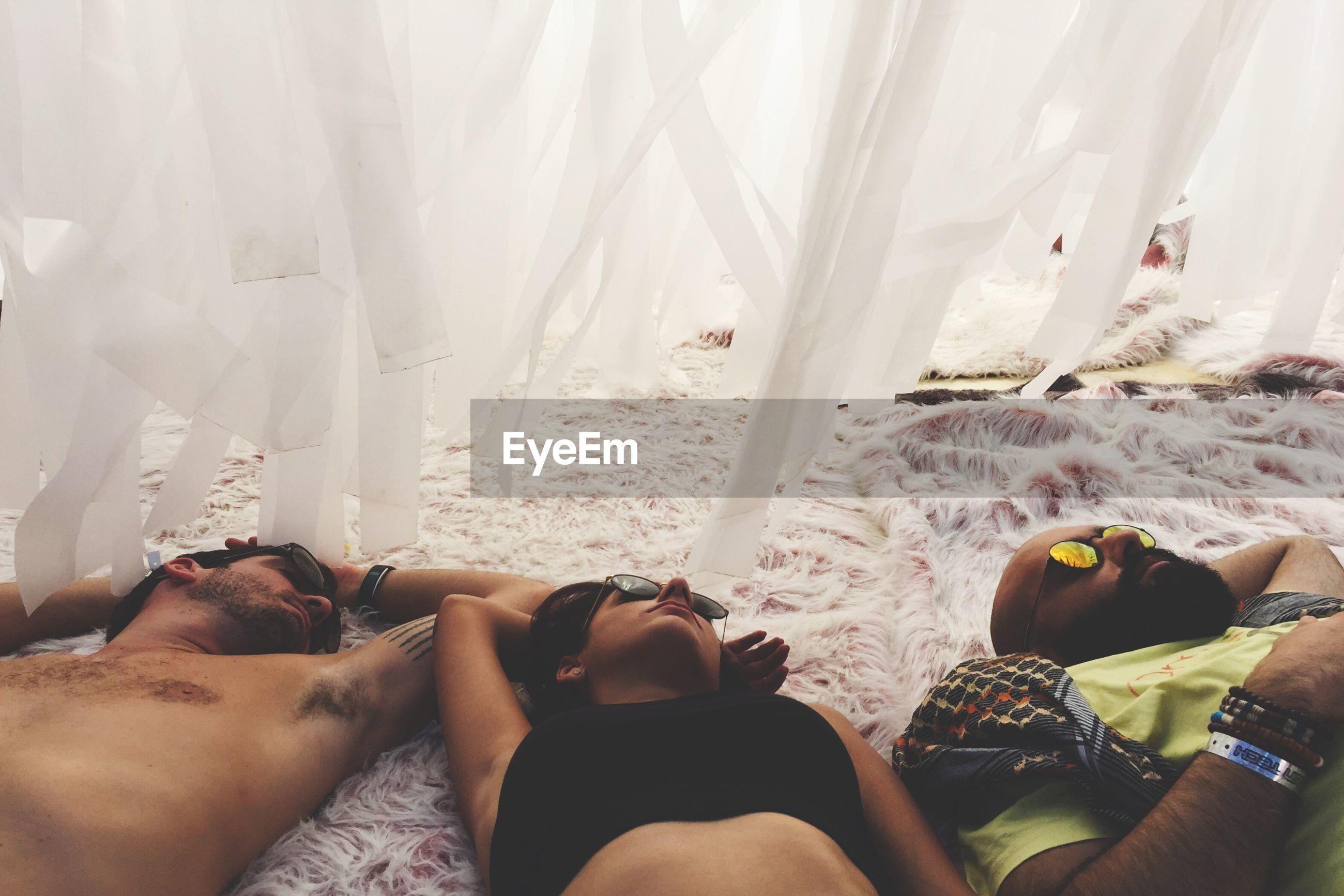 High angle view of friends sleeping on rug