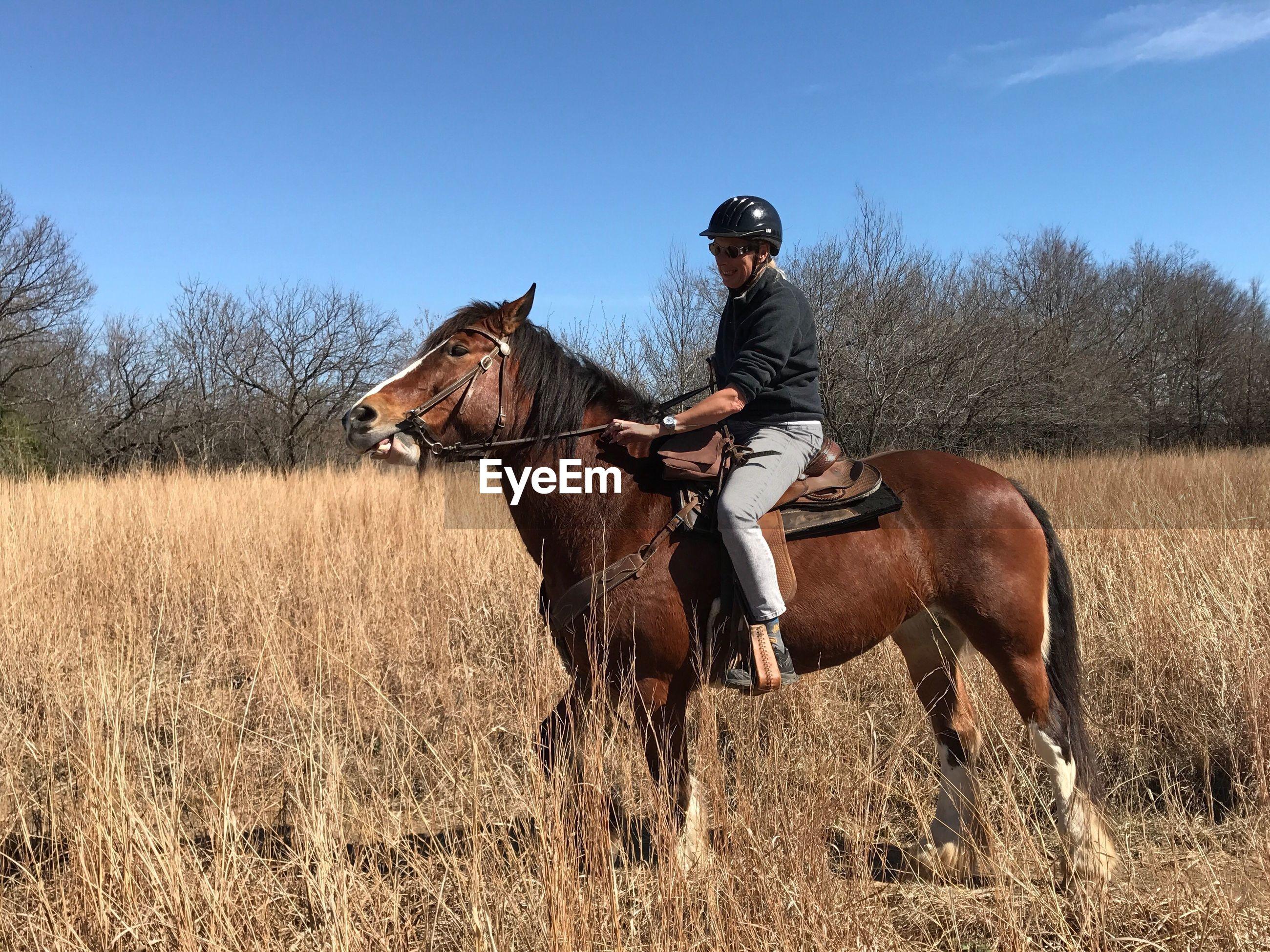 Happy woman wearing helmet riding horse on grassy field against sky