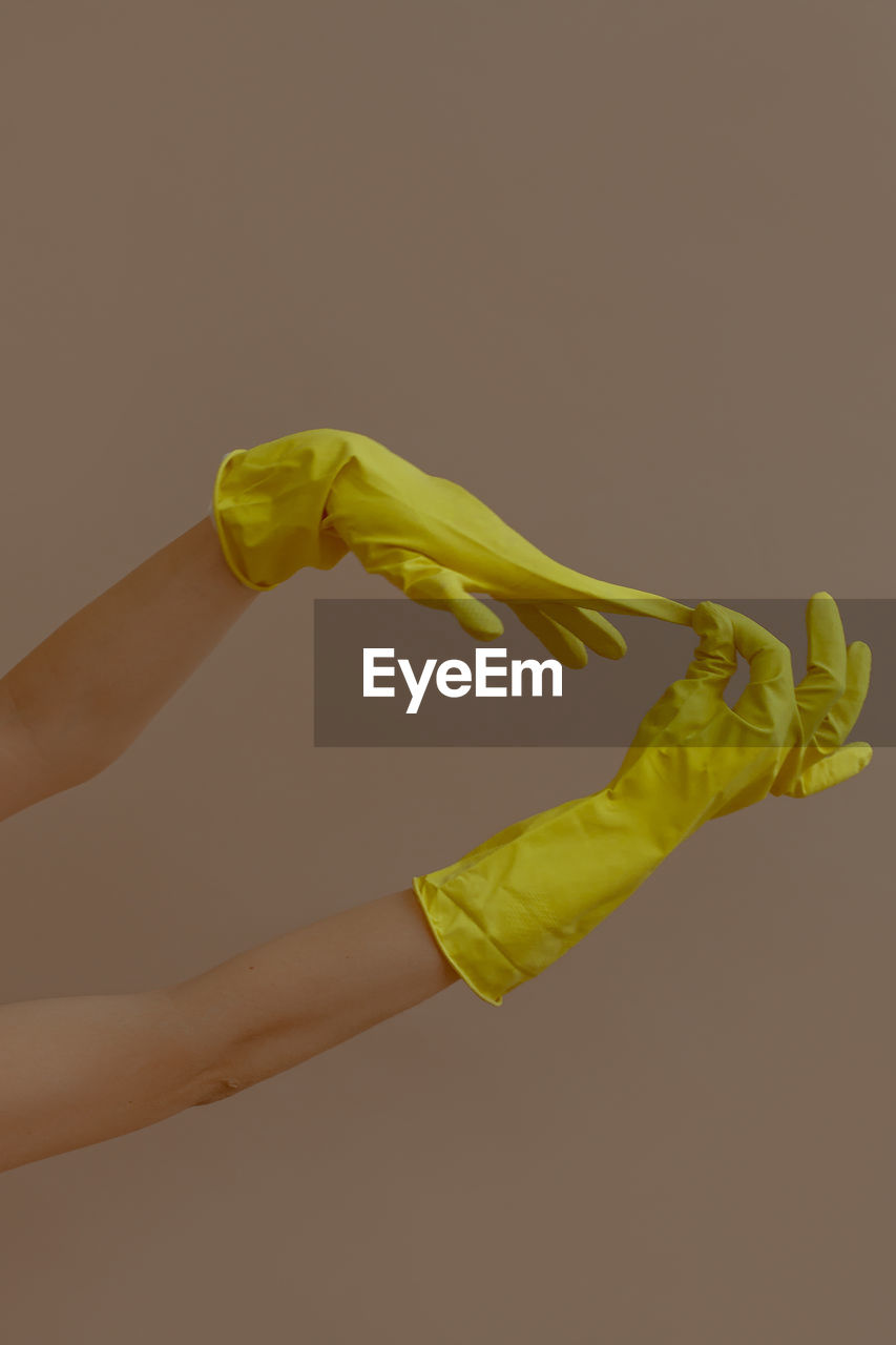 Cropped hands of person removing yellow gloves against beige background