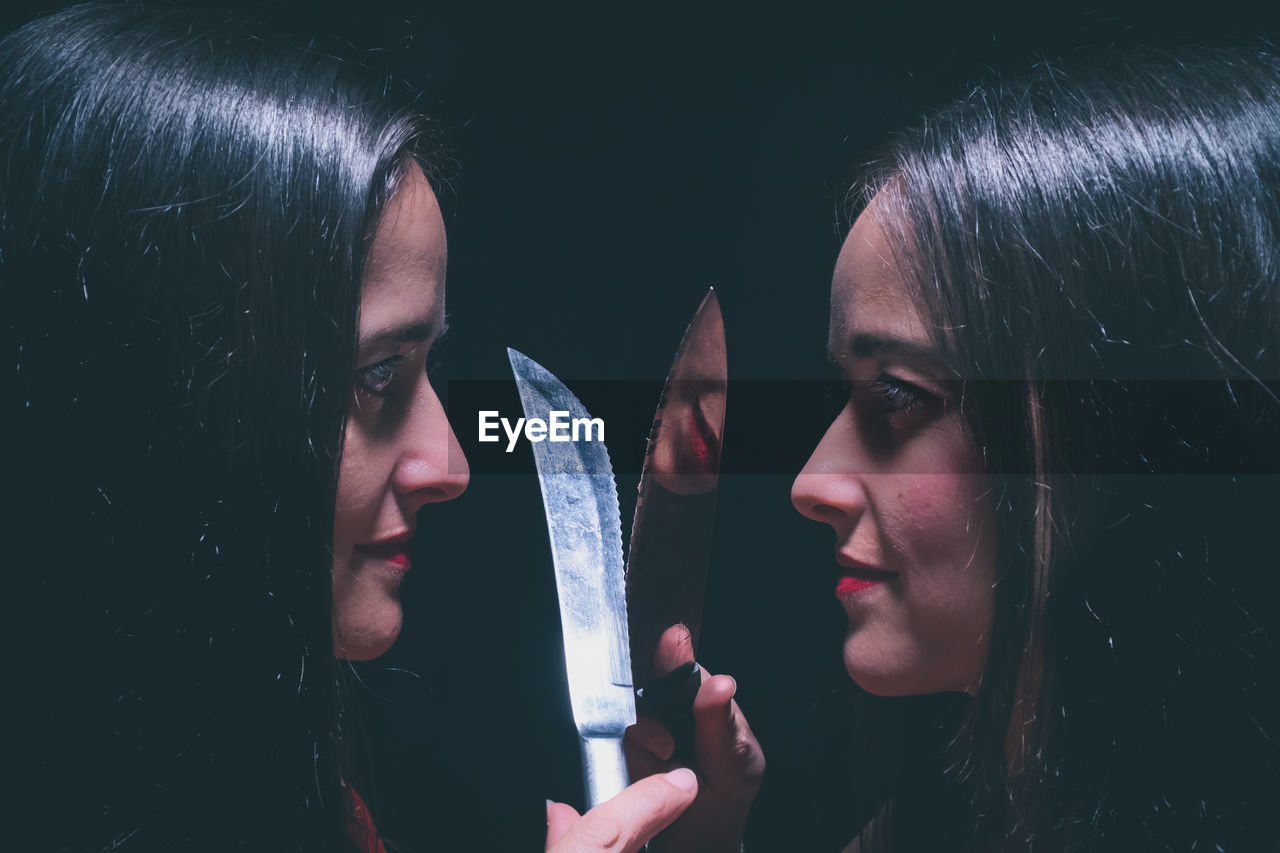 Sisters crossing knife against black background