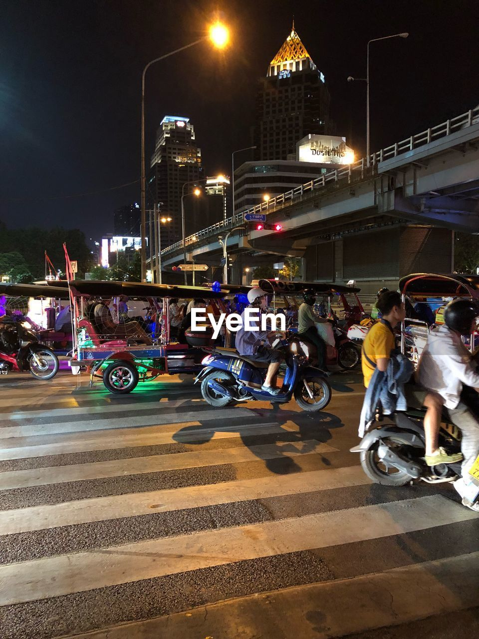transportation, city, mode of transportation, night, illuminated, architecture, land vehicle, street, built structure, building exterior, road, car, group of people, real people, street light, motorcycle, men, city life, motion, motor vehicle, outdoors, riding
