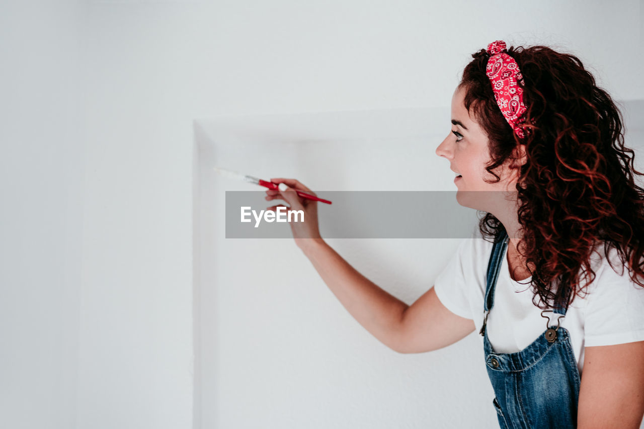 YOUNG WOMAN LOOKING AWAY WHILE STANDING ON WALL