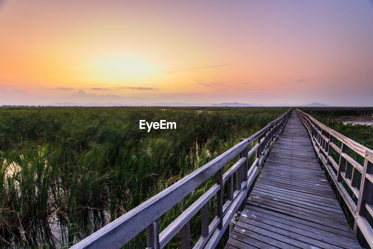 Wood Paneled Footbridge Along Countryside Landscape