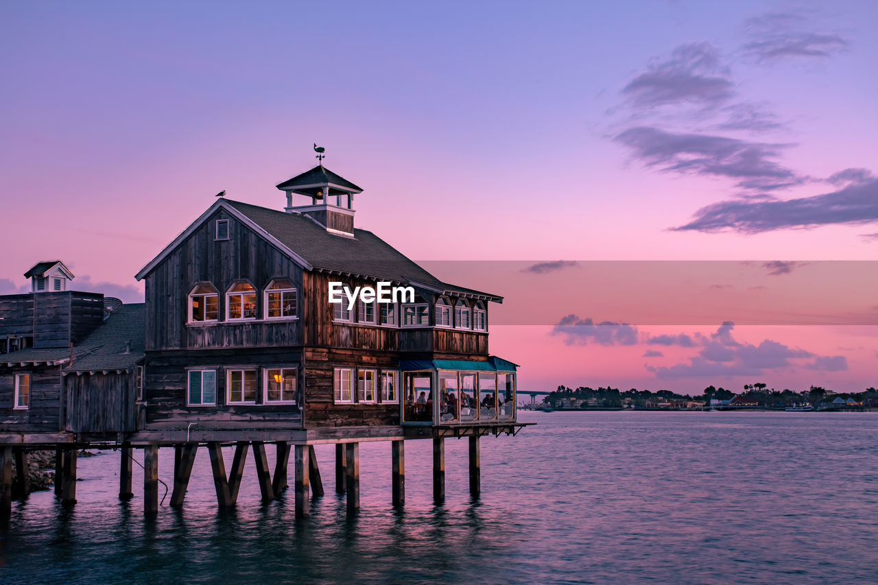 BUILDING BY SEA AGAINST SKY AT SUNSET