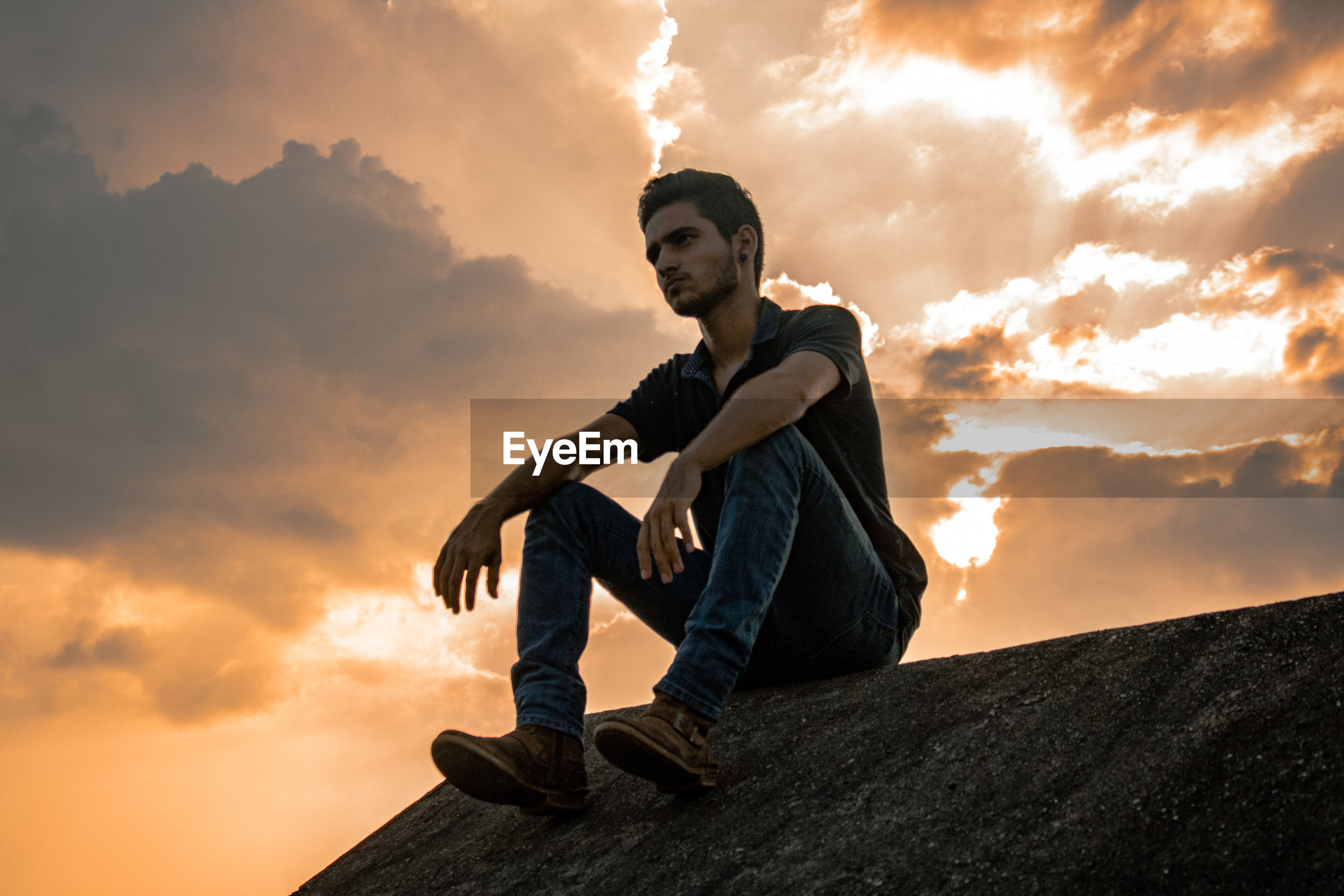 Low angle view of young man sitting against sky during sunset