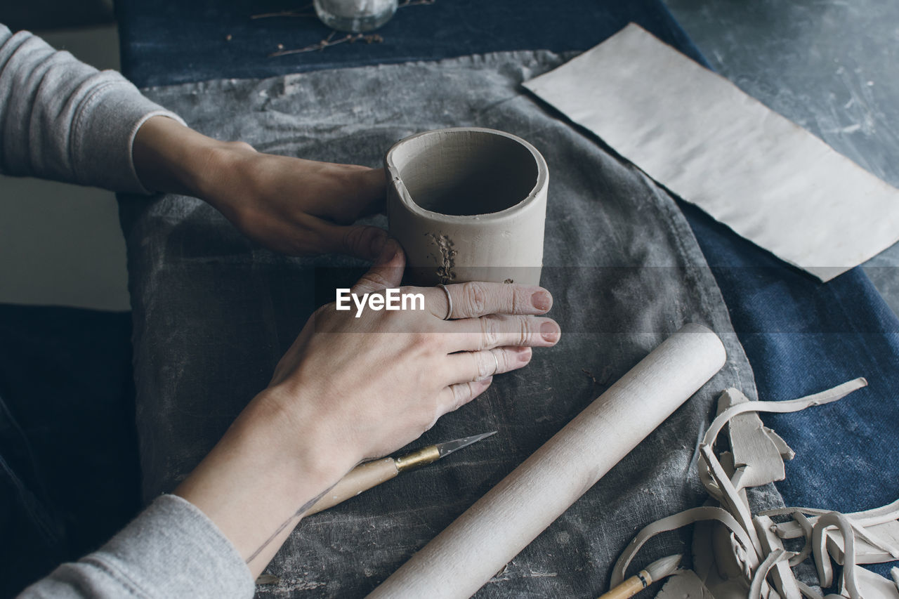 Cropped Image Of Hands Holding Cup