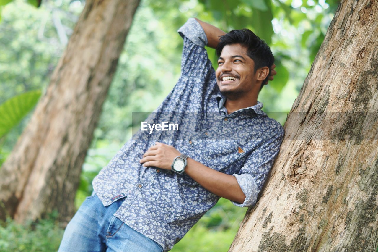 Happy young man standing by tree trunk in forest