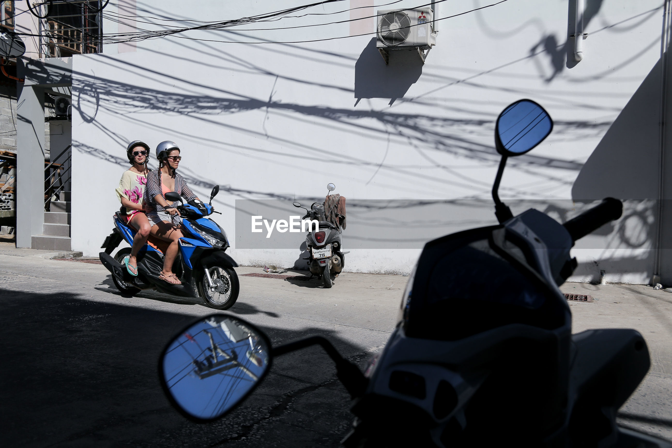 transportation, mode of transport, bicycle, land vehicle, hanging, travel, road, shadow, stationary, tourism, travel destinations, group of people, cable, day, outdoors, power line, parked, focus on foreground, vacations, biker