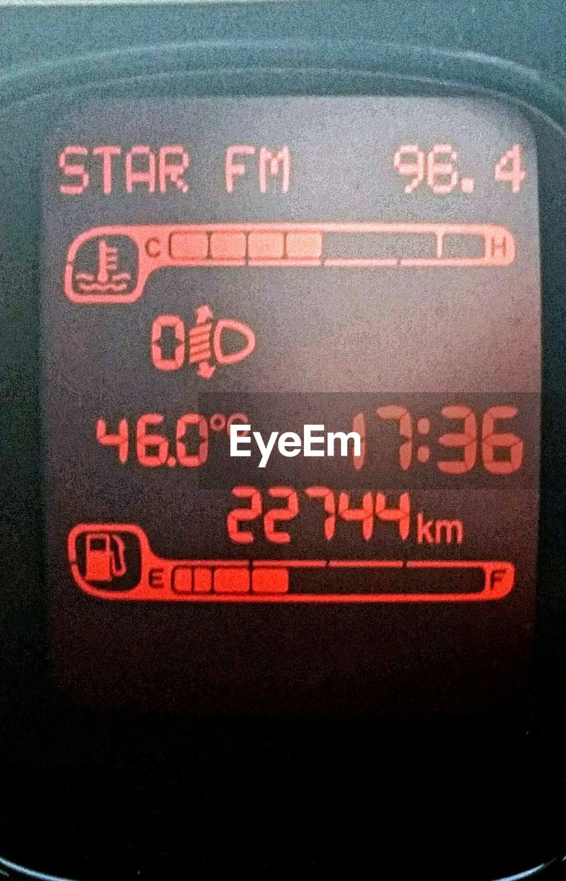 text, communication, no people, close-up, red, black color, indoors, control panel, speedometer, day