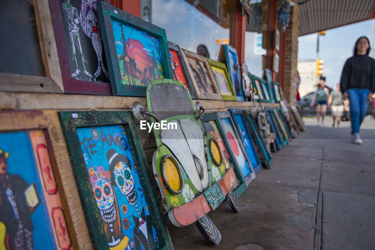 multi colored, art and craft, for sale, architecture, choice, creativity, incidental people, built structure, day, variation, graffiti, retail, in a row, large group of objects, focus on foreground, wall - building feature, market stall, people, outdoors, arrangement, retail display