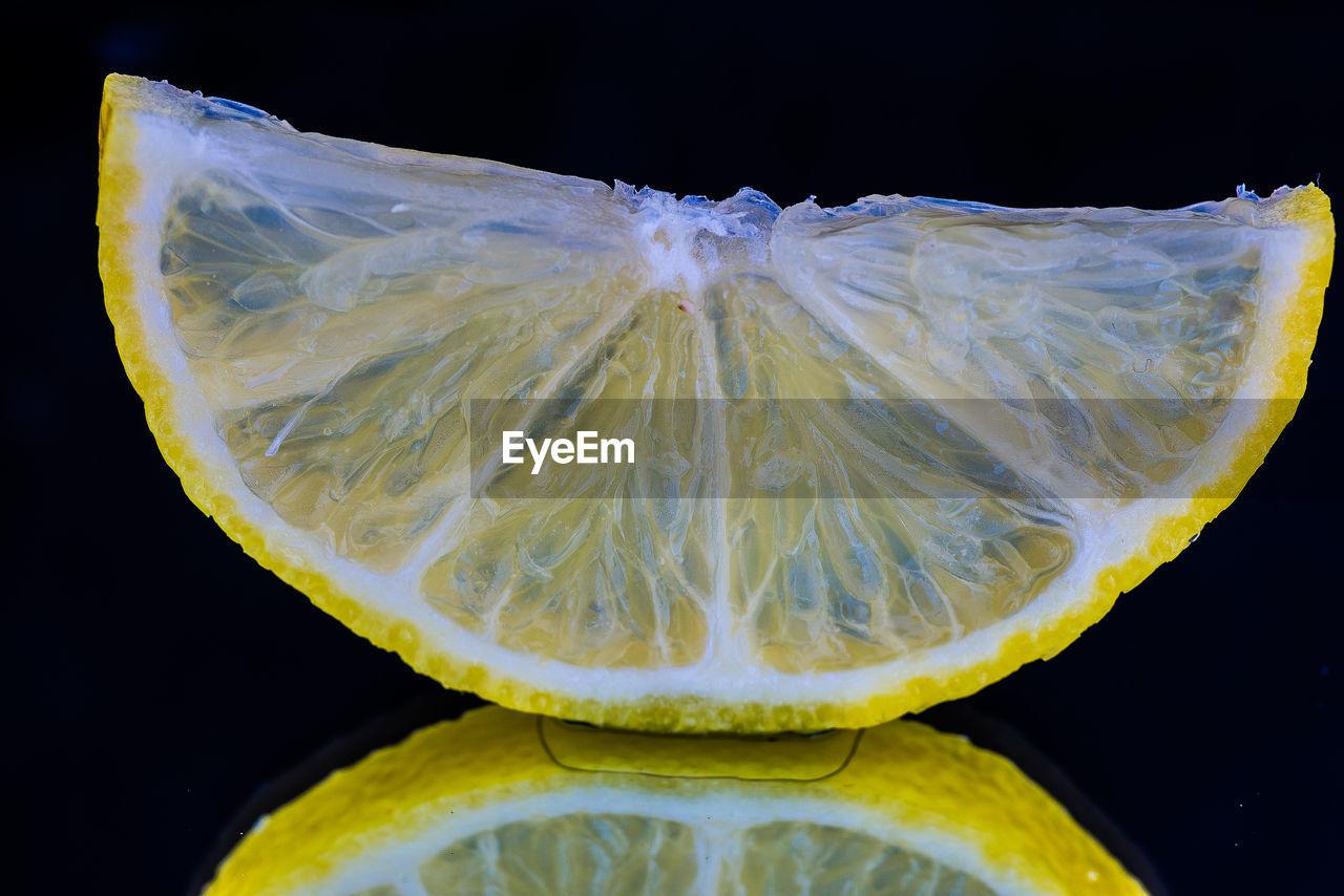Close-Up Of Lemon Slice Against Black Background
