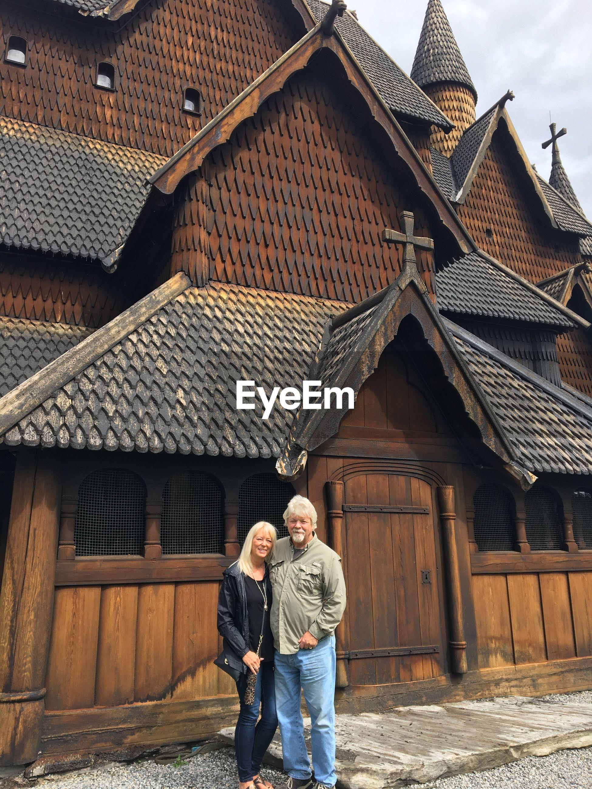 Full length of senior couple standing against church