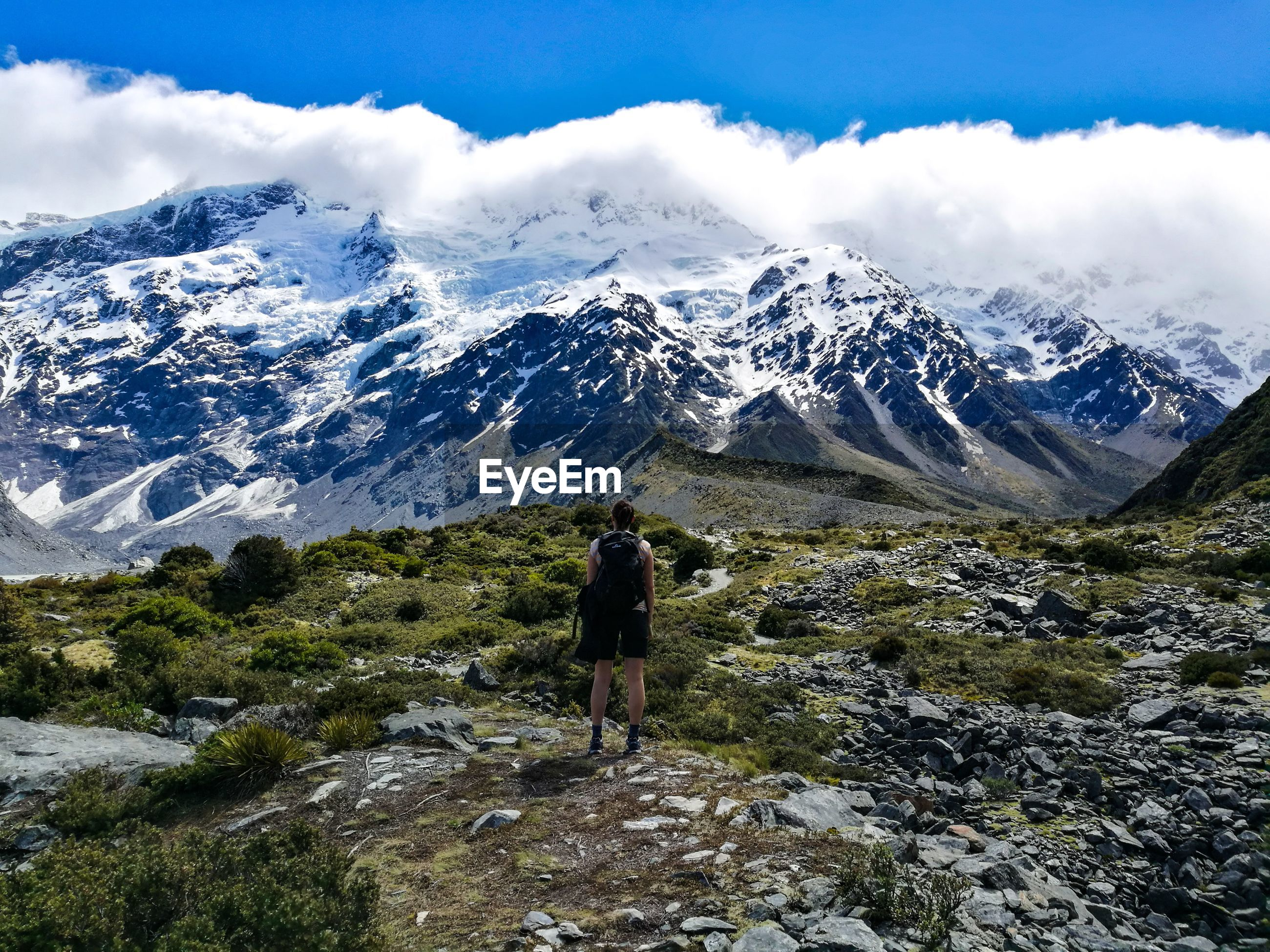 Rear view of female hiker standing against snowcapped mountain