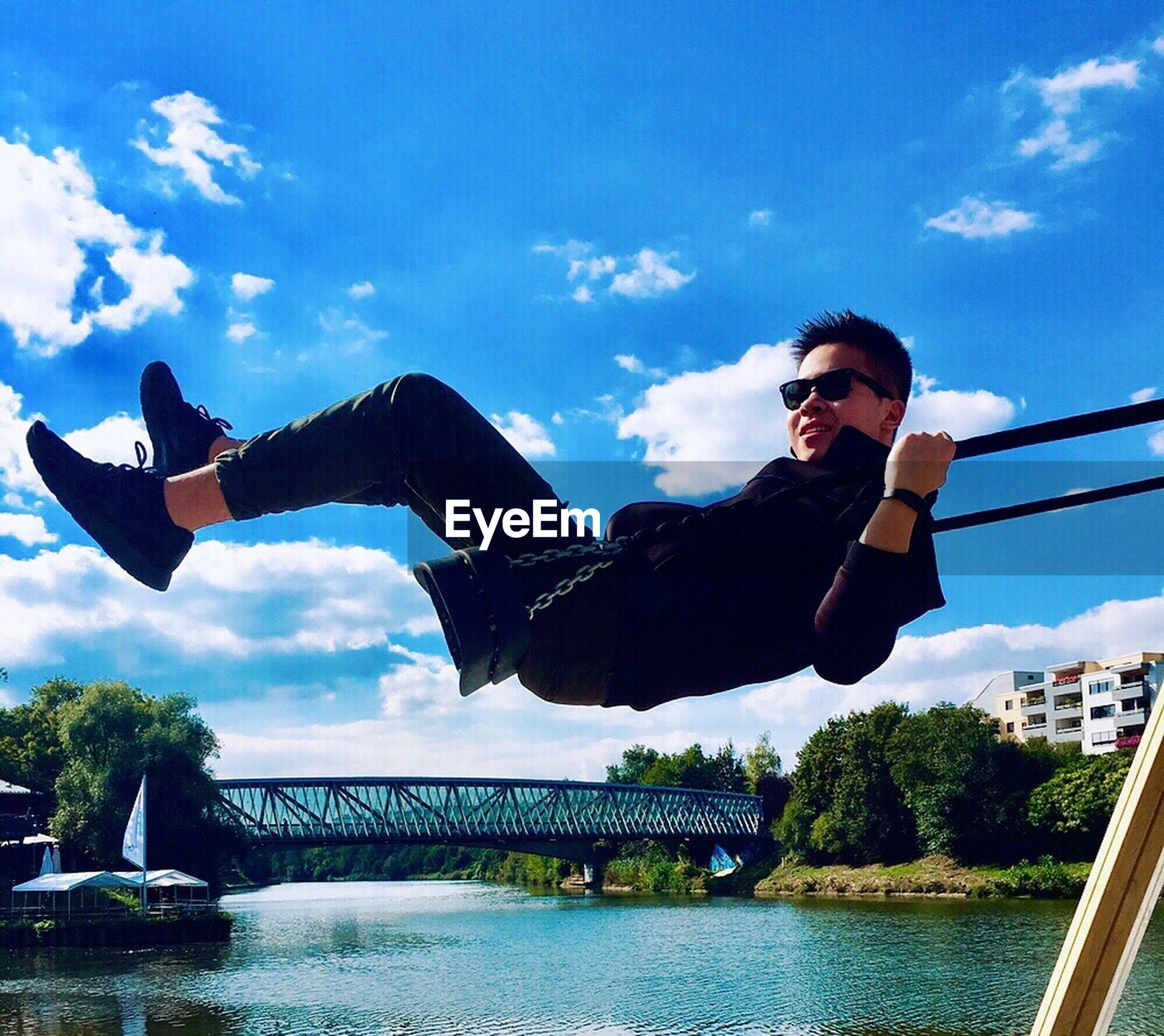 full length, leisure activity, lifestyles, casual clothing, sky, water, enjoyment, person, young adult, motion, fun, bridge - man made structure, river, cloud - sky, vitality, waterfront, mid-air, day, joy, outdoors