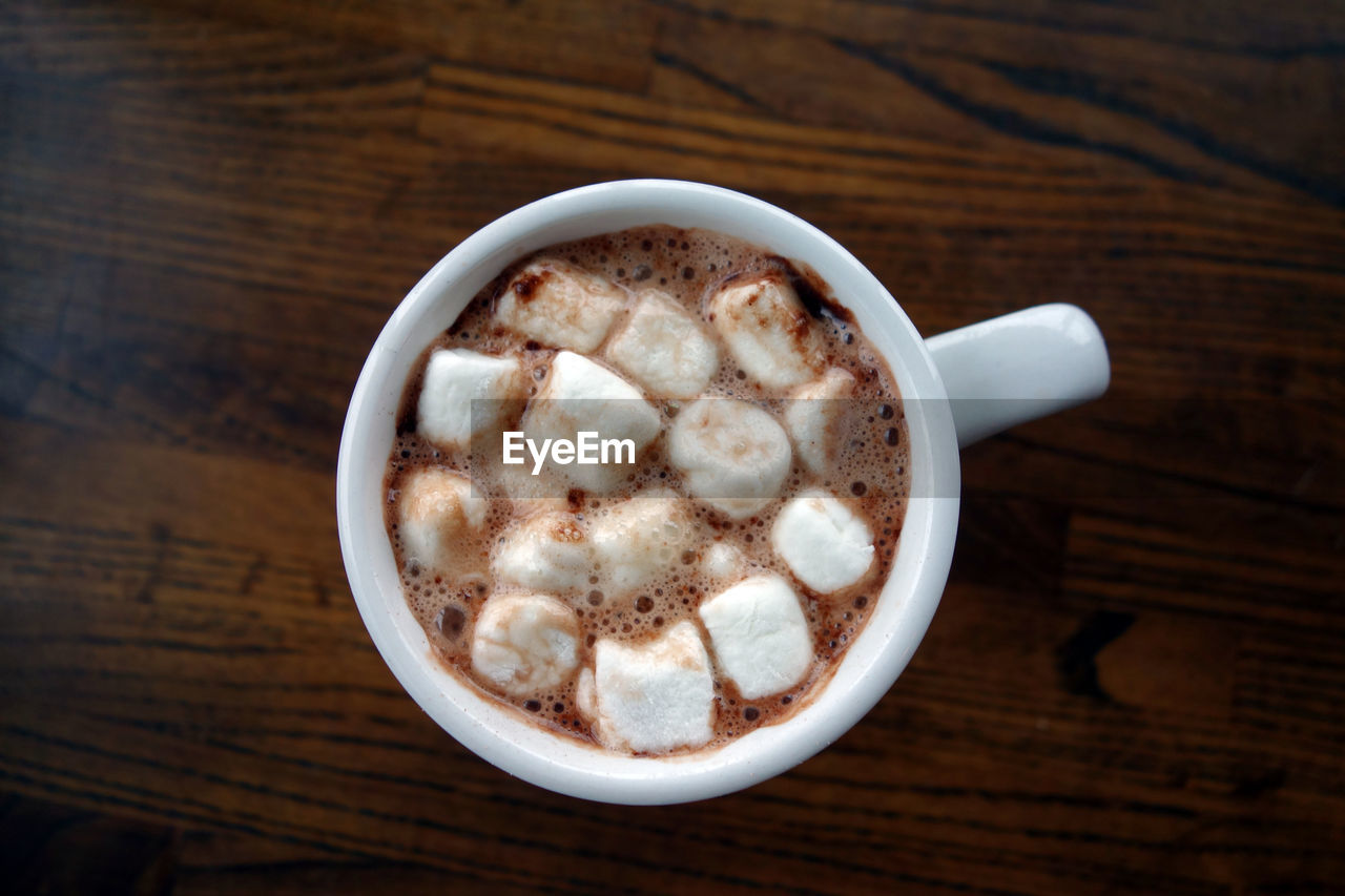 Directly above view of fresh marshmallows in coffee cup on table