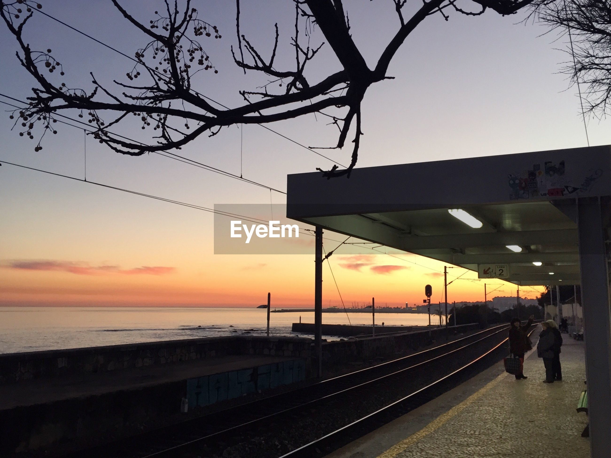 Railroad station by sea during sunset