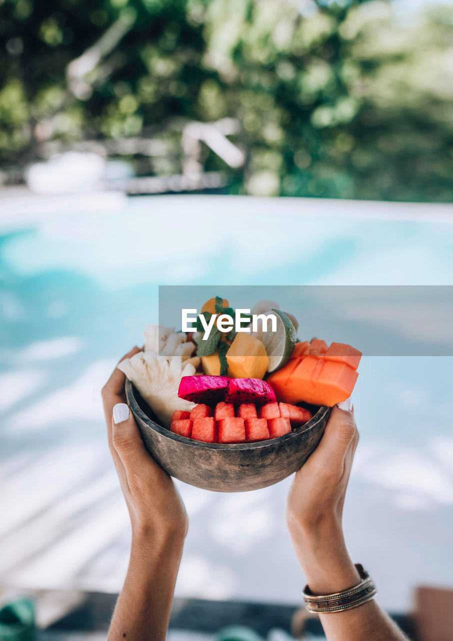 A woman is holding a healthy fruit bowl.