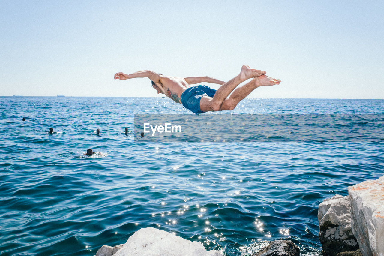 sea, water, full length, clear sky, jumping, mid-air, men, horizon over water, outdoors, day, vitality, nature, one person, upside down, excitement, handstand, energetic, shirtless, real people, blue, summer, flexibility, beauty in nature, swimming, young adult, sky, people