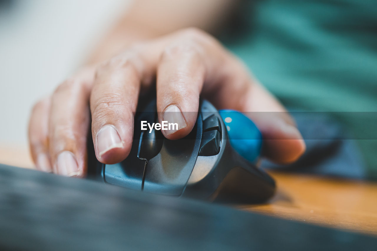 Close-up of woman hand using computer mouse at desk