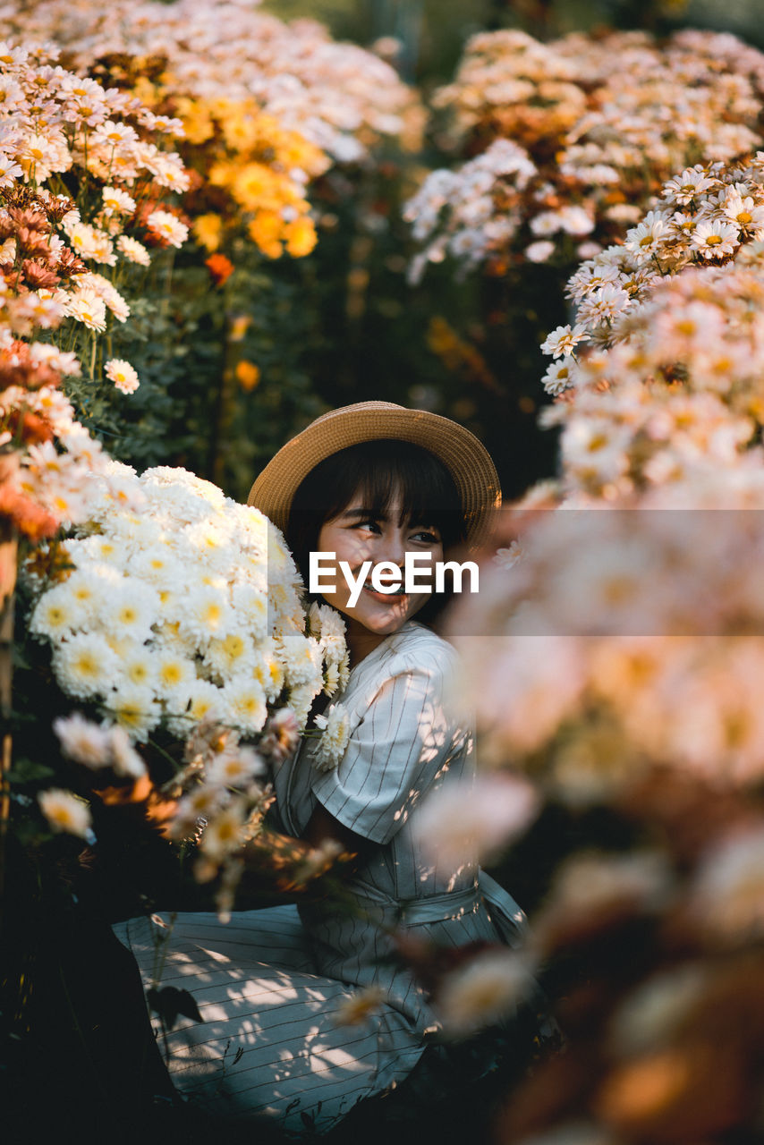 hat, real people, one person, plant, portrait, lifestyles, selective focus, leisure activity, flowering plant, flower, clothing, childhood, child, looking at camera, day, standing, nature, front view, outdoors