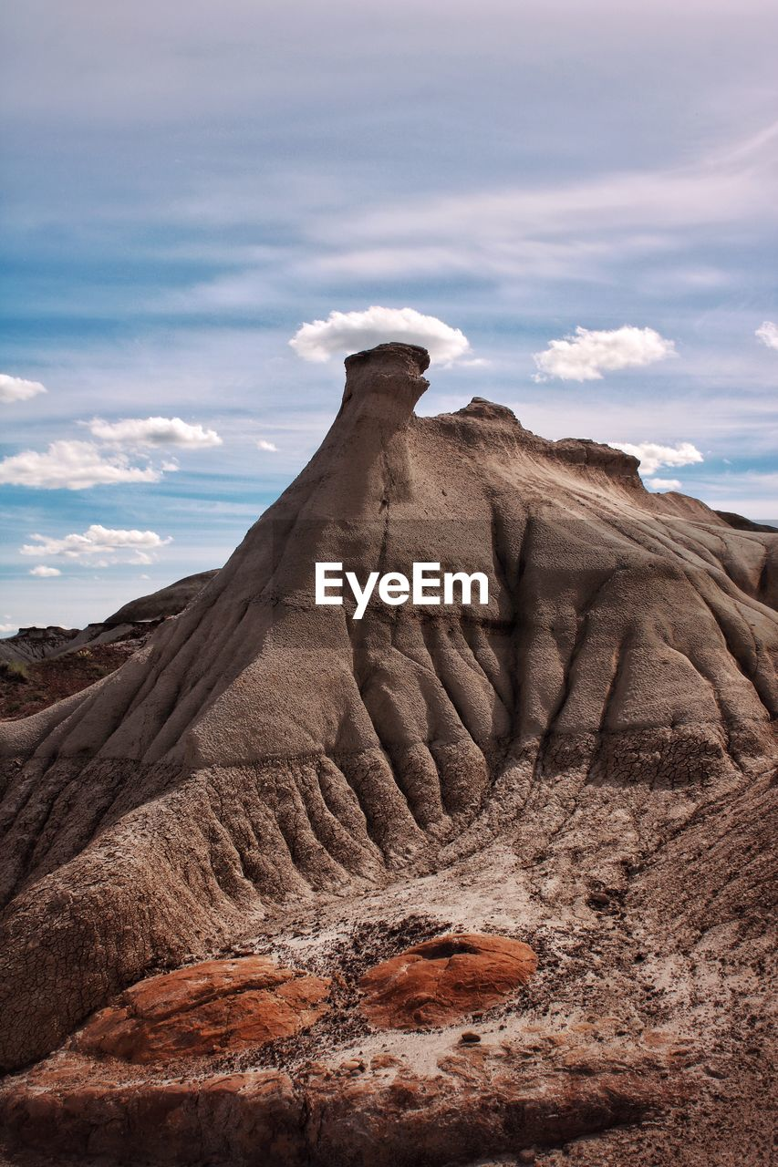 Hoodoo rock formations on landscape against cloudy sky