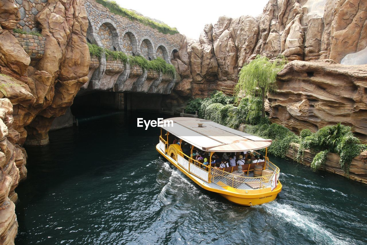 water, rock, transportation, rock formation, rock - object, solid, nautical vessel, day, mode of transportation, travel, river, travel destinations, nature, architecture, beauty in nature, waterfront, tourism, built structure, cliff, arch, outdoors, formation