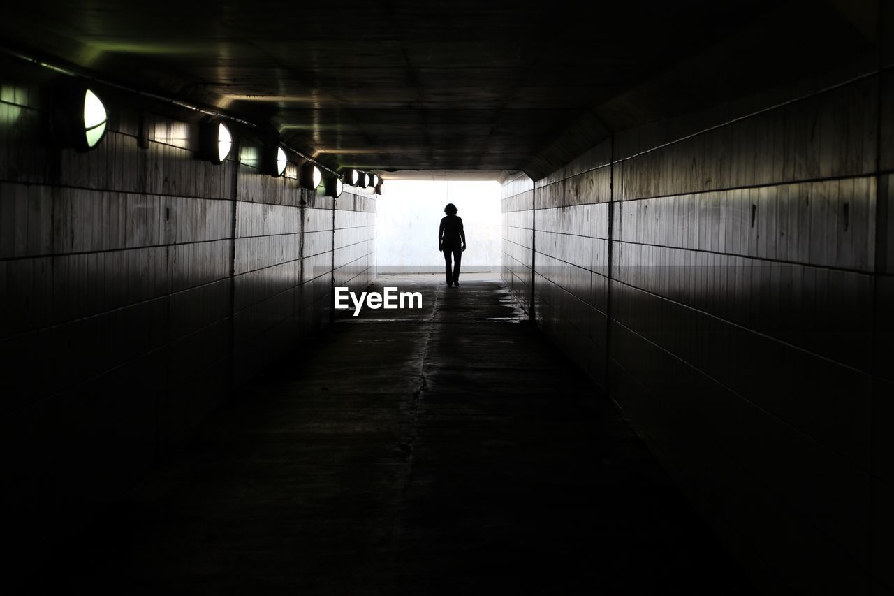 Rear View Of Person Walking In Tunnel