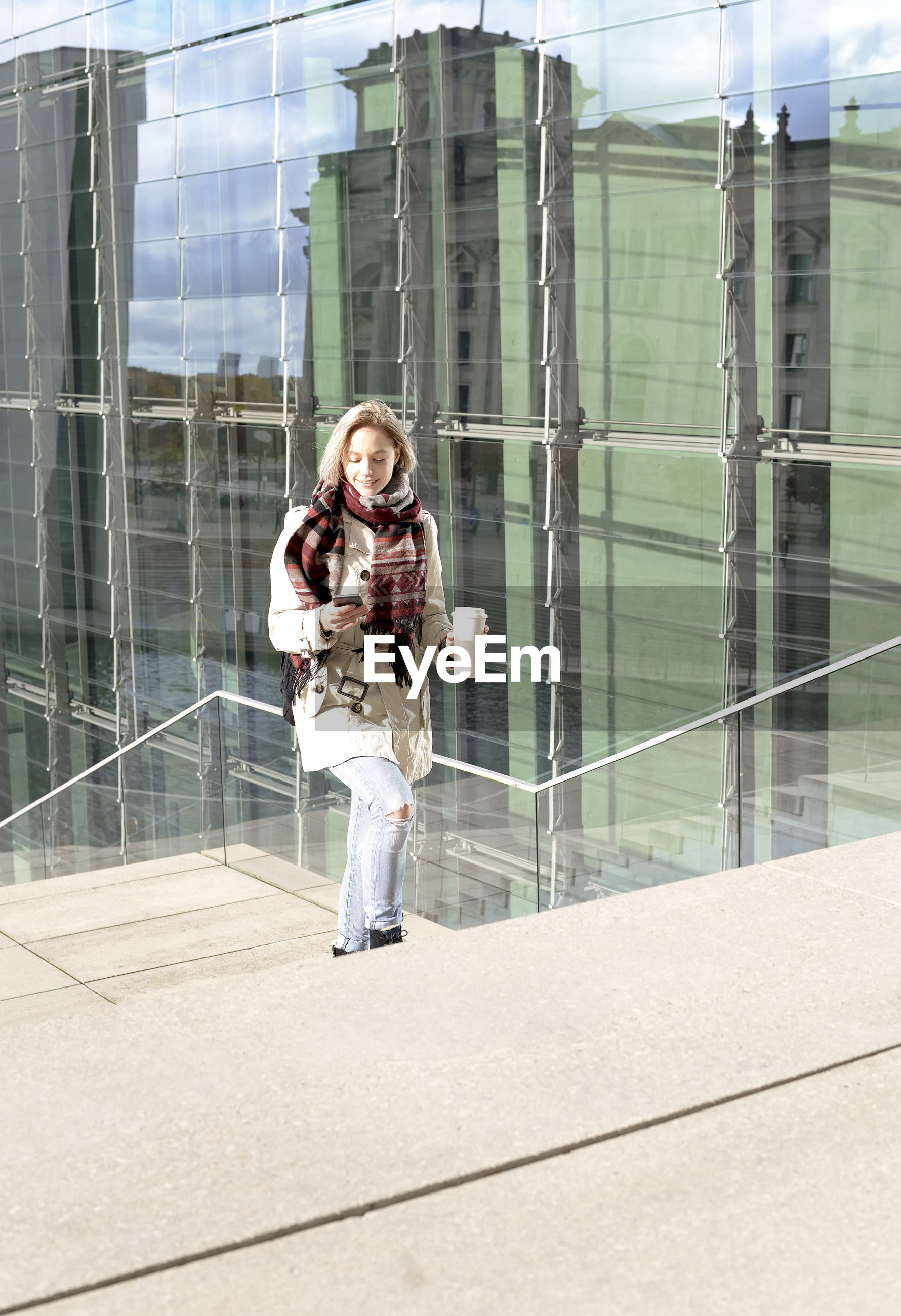 Full length of smiling young woman using mobile phone while climbing steps
