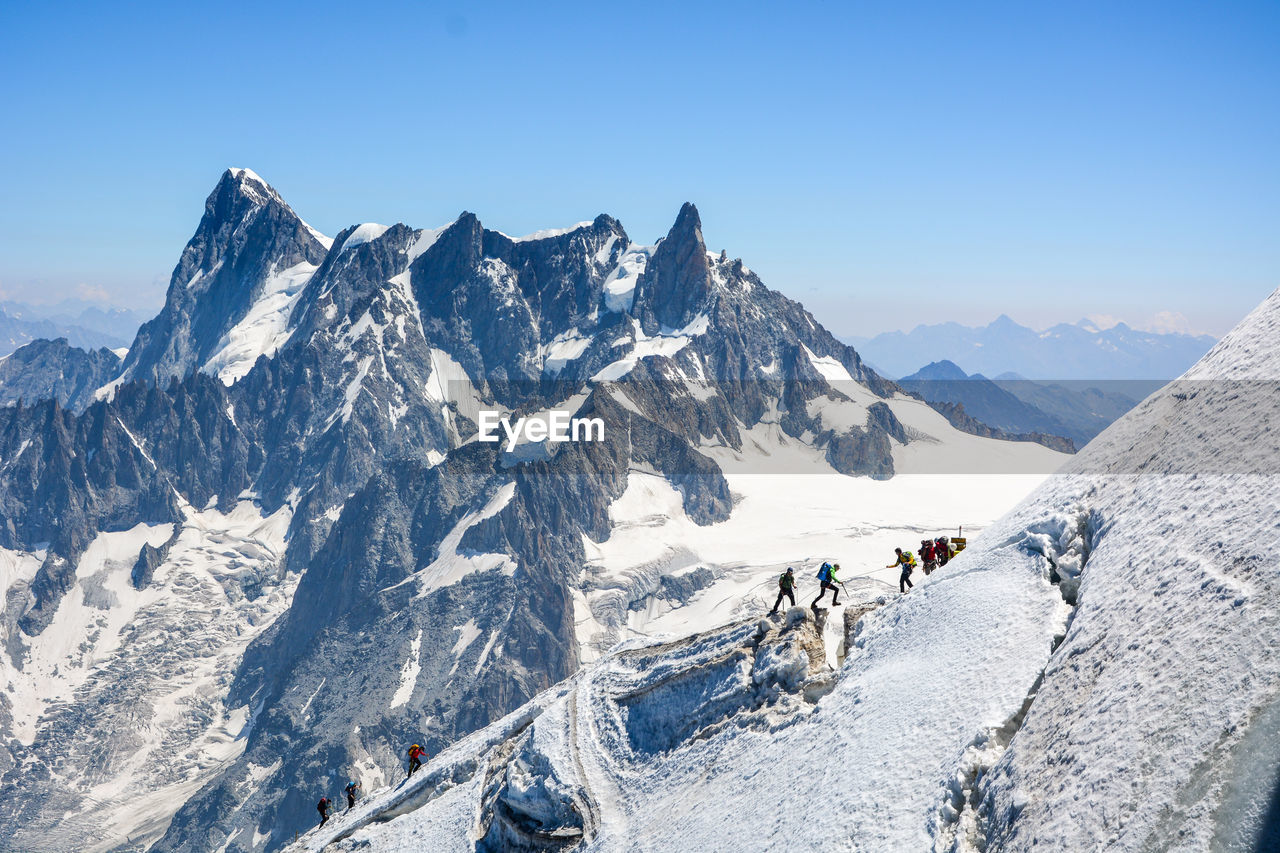 People Hiking On Snowcapped Mountains Against Clear Sky