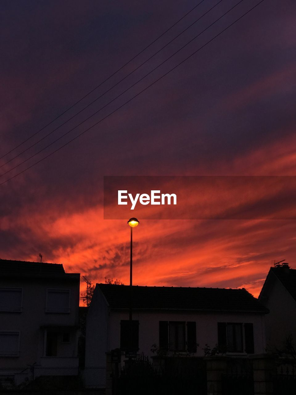 building exterior, sky, architecture, built structure, sunset, cloud - sky, orange color, building, silhouette, no people, nature, city, dusk, residential district, low angle view, technology, outdoors, electricity, cable, dramatic sky, romantic sky, power supply