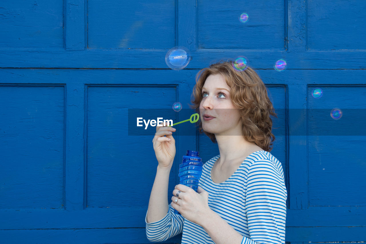 Playful Woman Blowing Bubbles While Standing Against Door