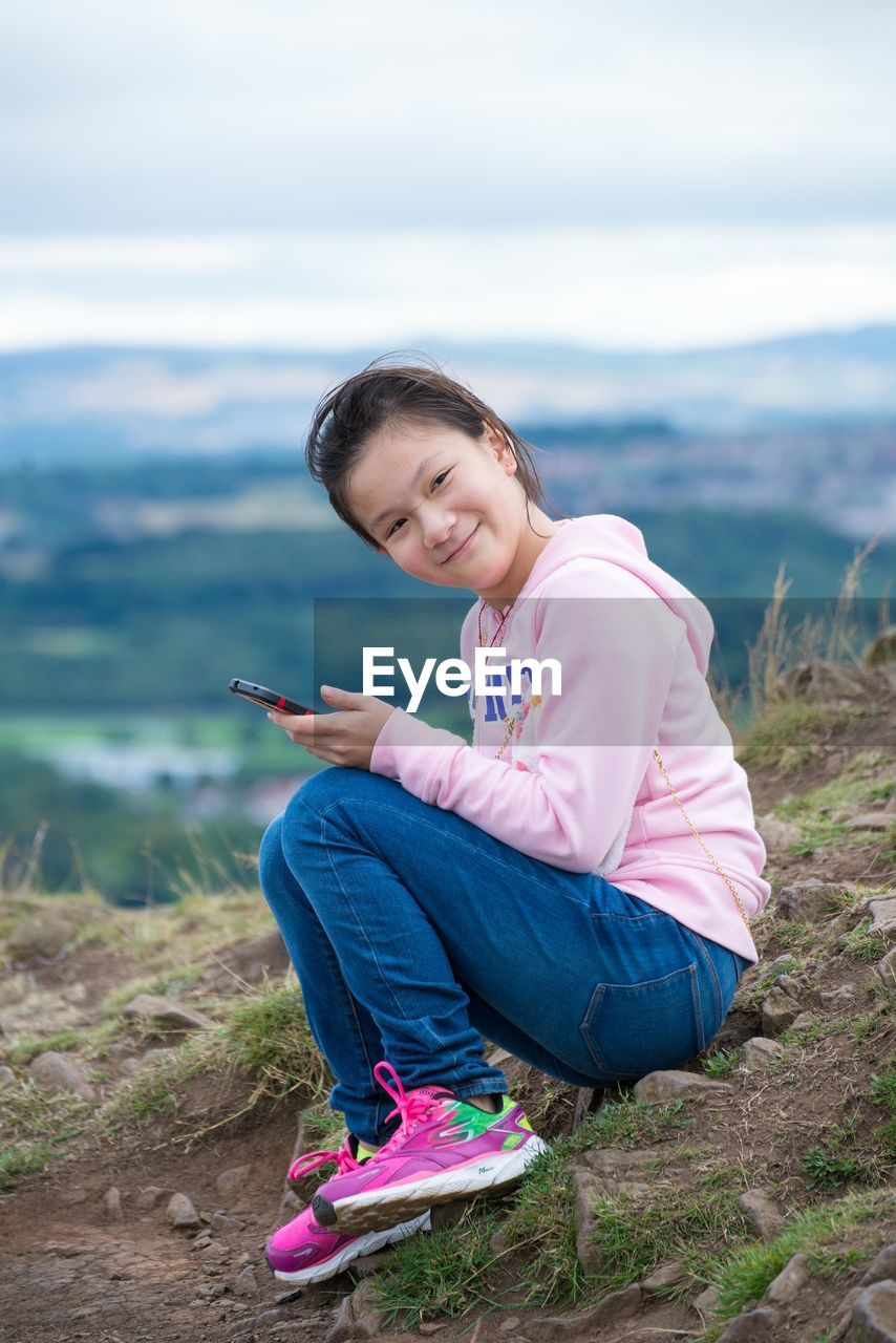 Side View Full Length Portrait Of Girl With Mobile Phone Sitting On Mountain