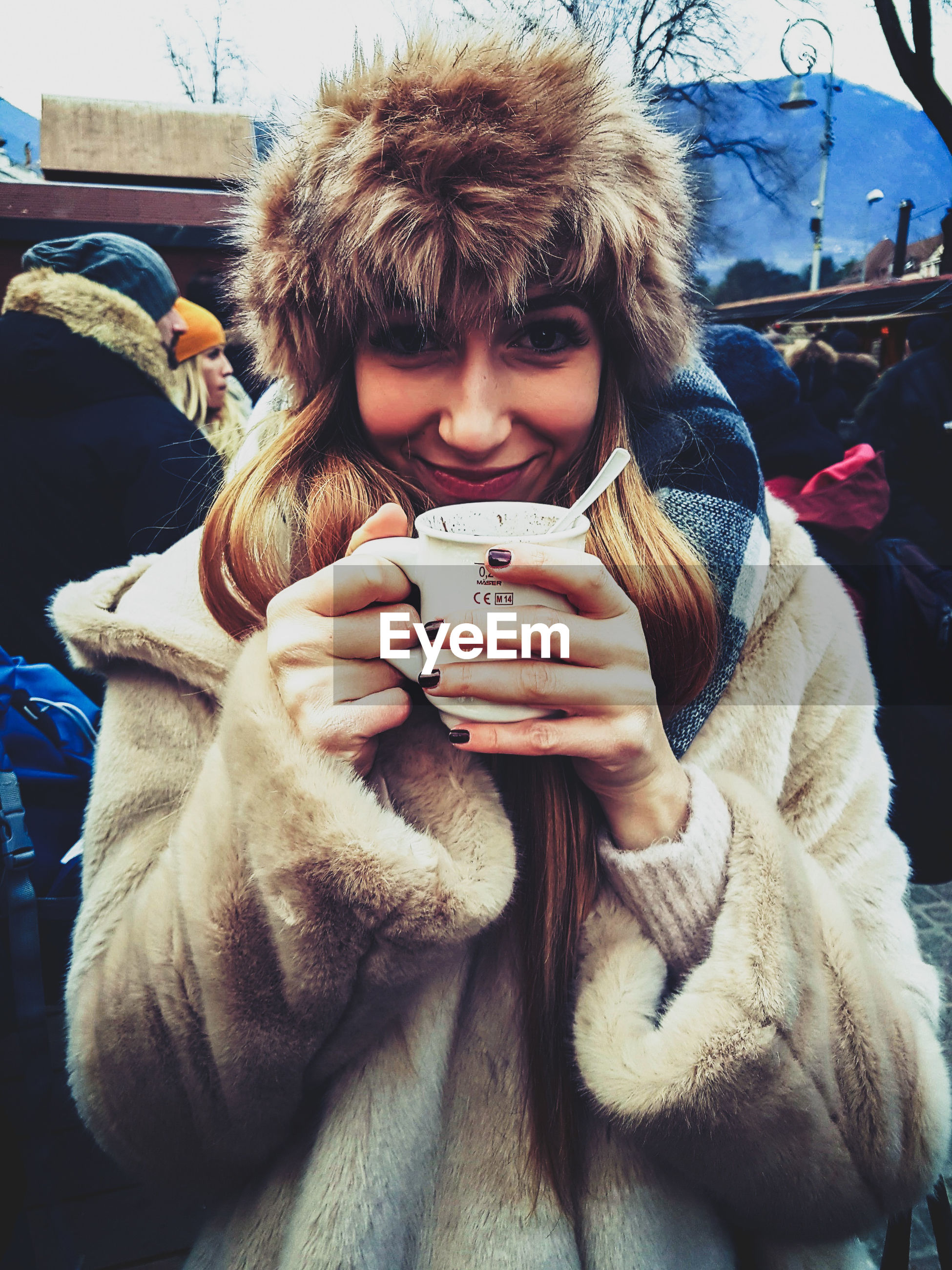 PORTRAIT OF YOUNG WOMAN DRINKING WHILE HOLDING SMART PHONE DURING WINTER
