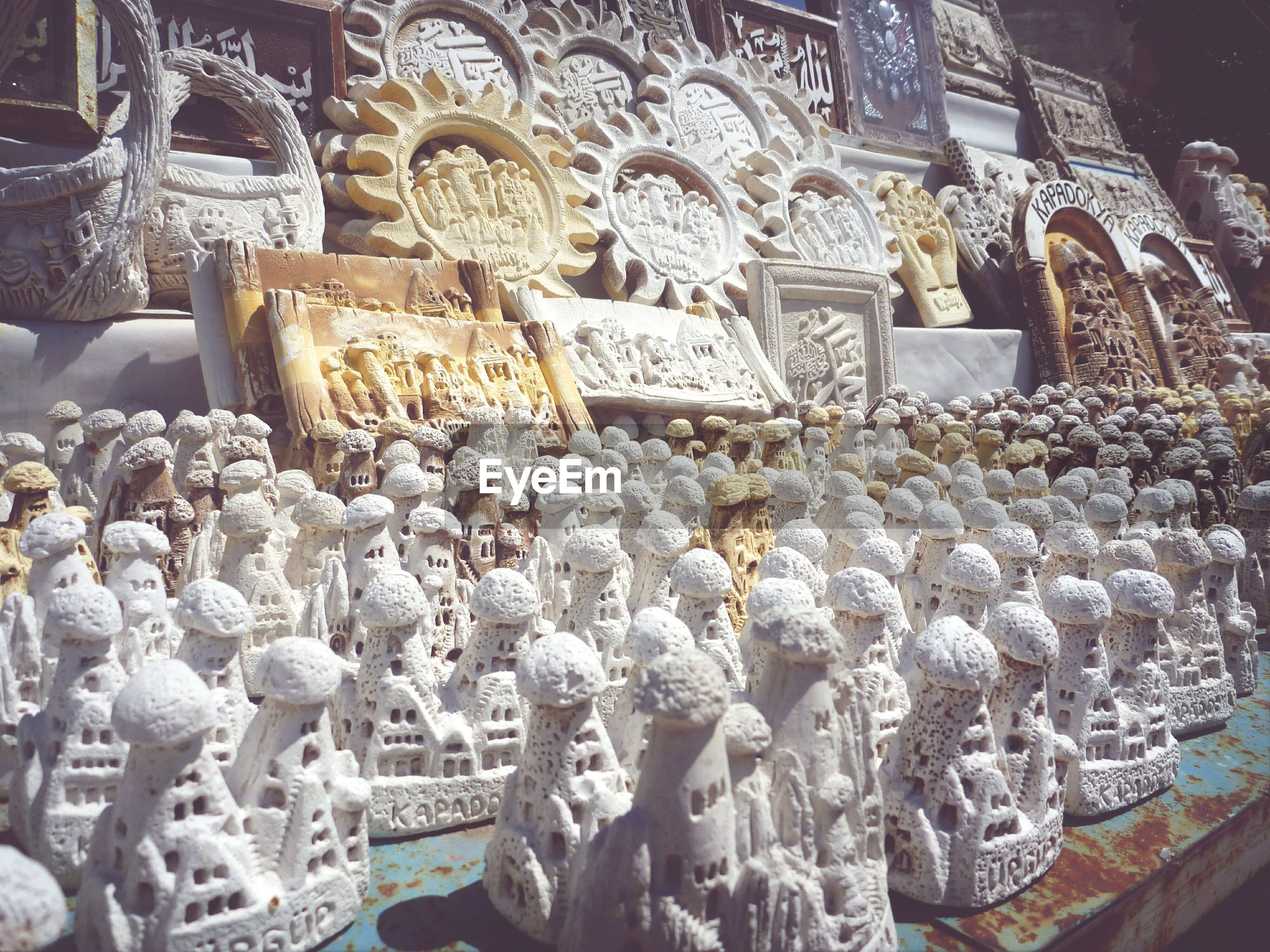 large group of objects, abundance, for sale, arrangement, indoors, in a row, retail, hanging, religion, market stall, market, choice, spirituality, variation, order, white color, cultures, place of worship, no people, side by side