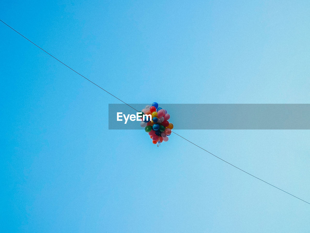Low Angle View Of Balloons Hanging On String Against Blue Sky