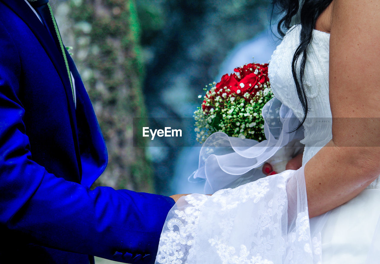 real people, midsection, outdoors, flower, two people, women, wedding, day, men, human hand, lifestyles, togetherness, leisure activity, celebration, groom, bride, nature, bonding, close-up, human body part, bouquet, bridegroom, wedding dress, tree, freshness