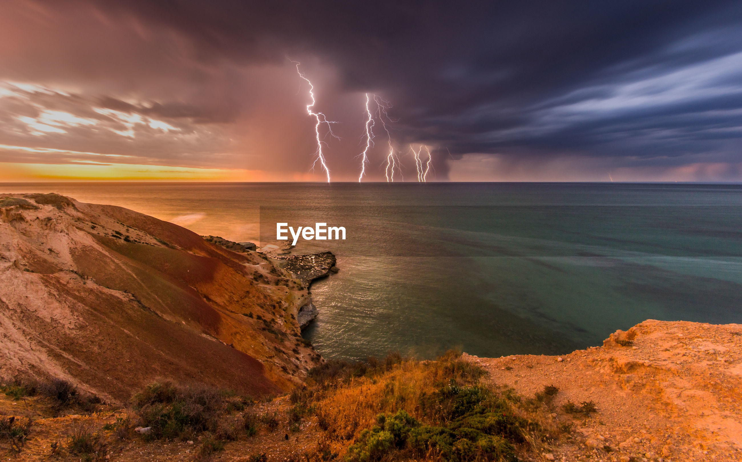 Scenic view of lightning over sea during sunset