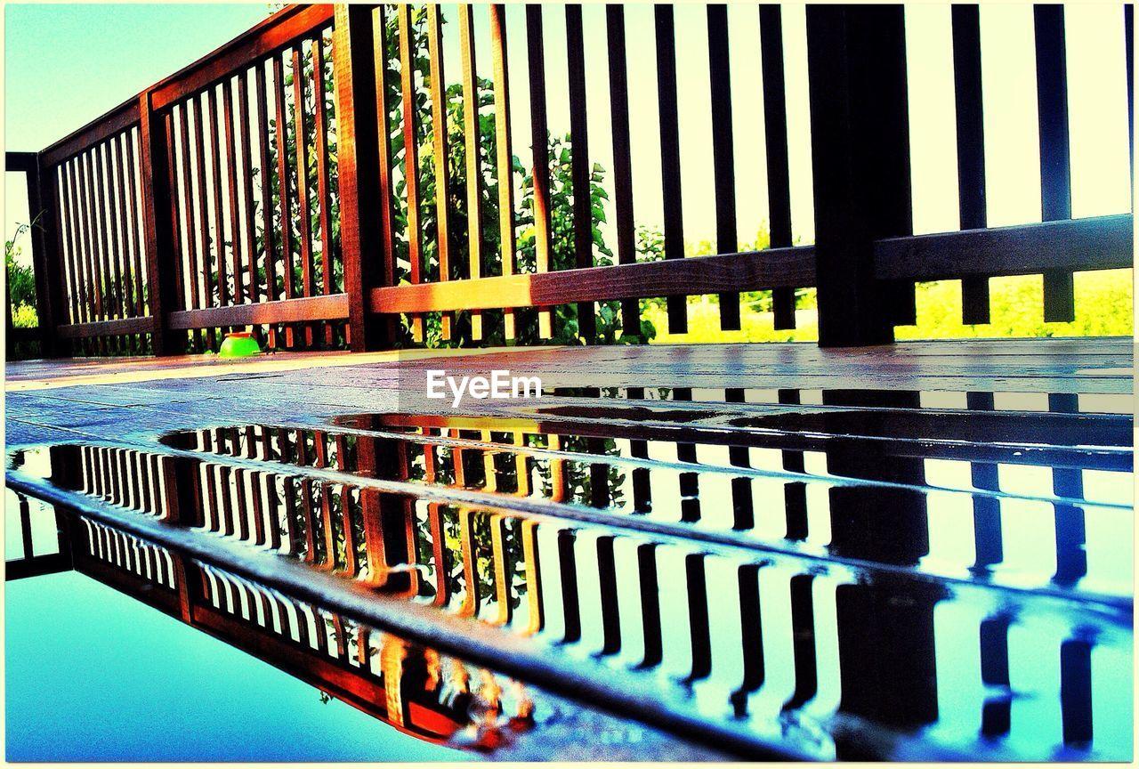 Reflection of railing on puddle