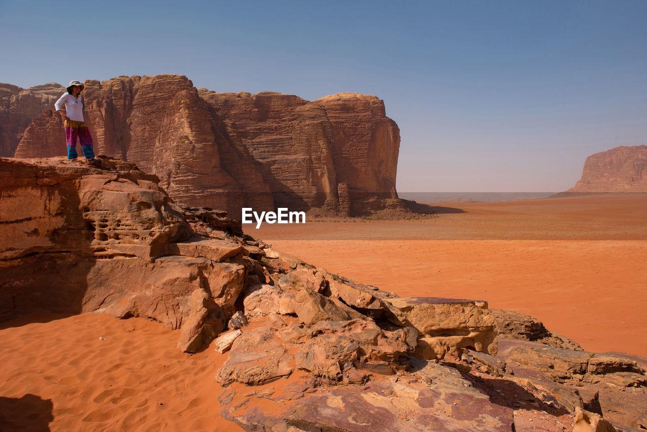 Woman standing on rock at desert against sky