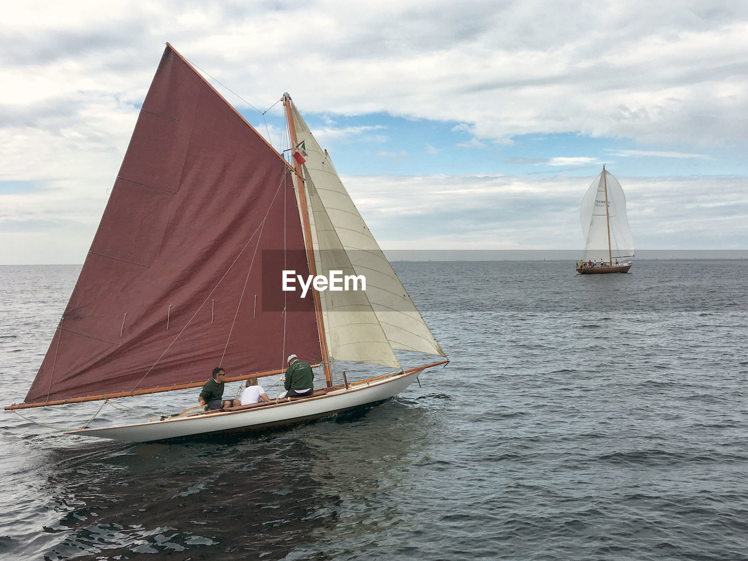 People sitting in sailboat on sea against sky