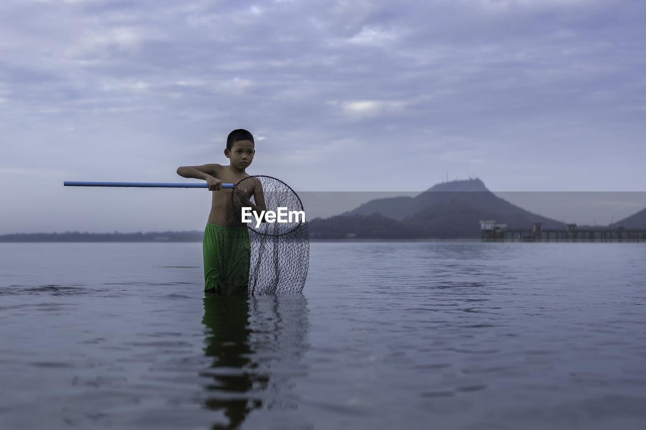 Boy holding fishing net in sea