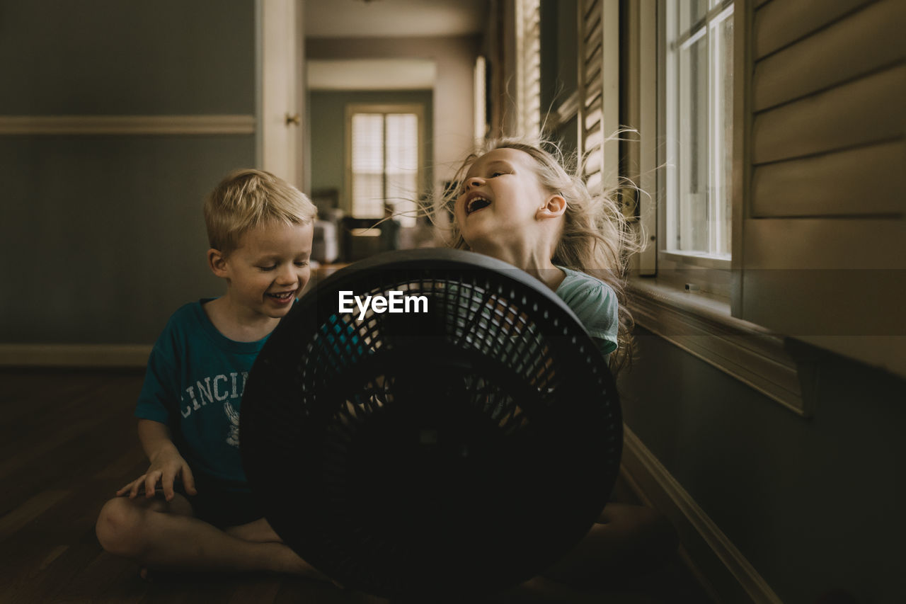 Children Sitting In Front Of Fan