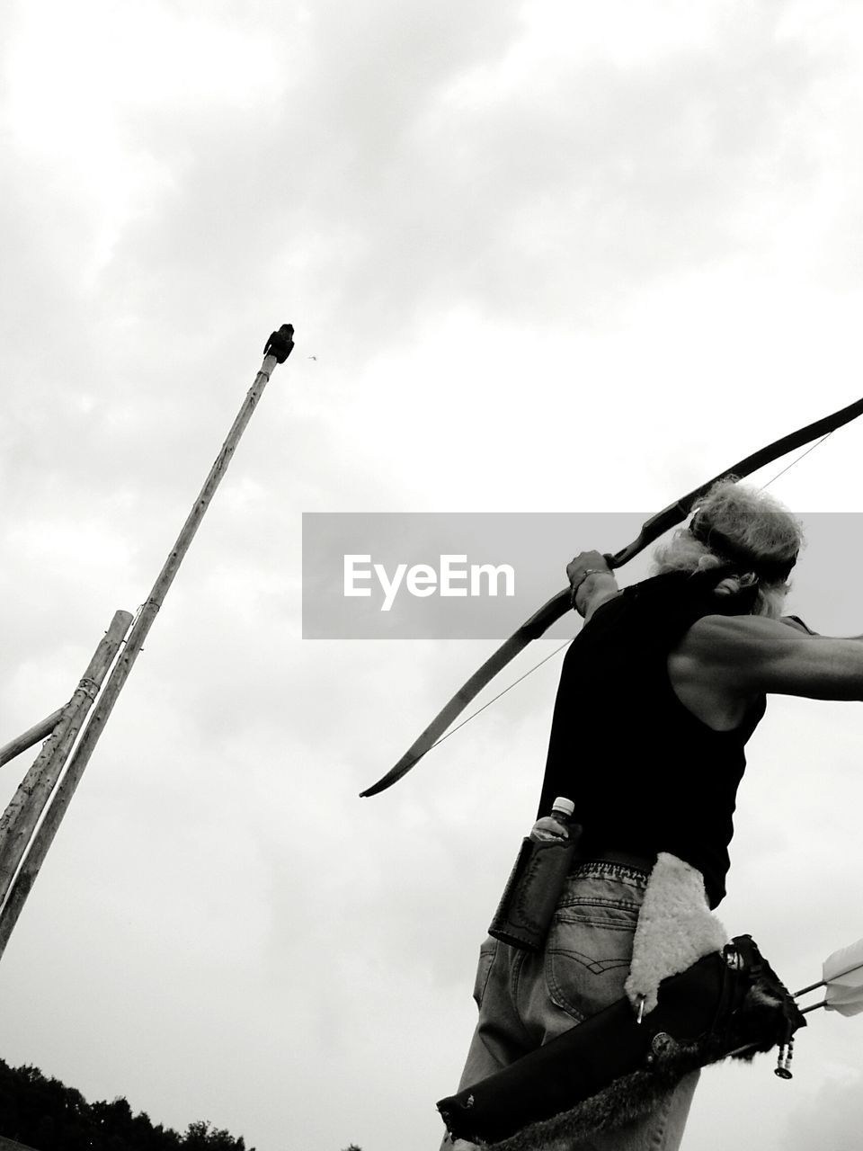 Low Angle View Of Man Aiming Bow And Arrow Against Sky